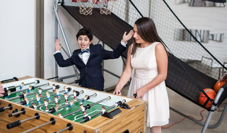 WJC Mitzvahs people playing fooseball